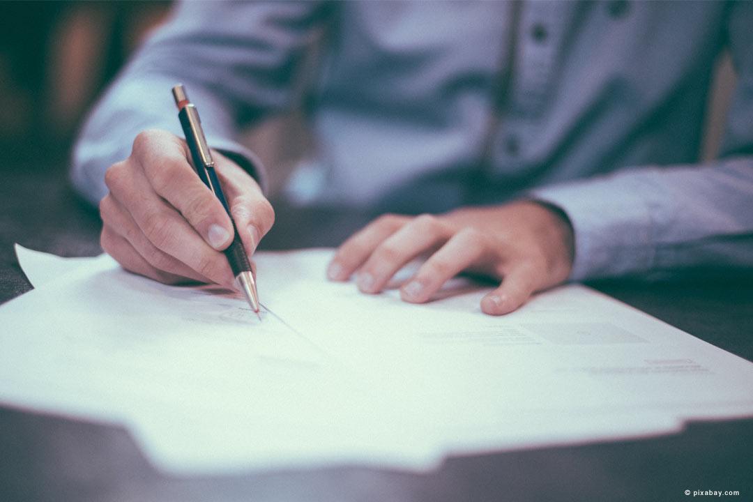 Mann schreibt auf Papier