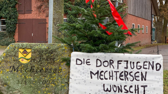 Weihnachtsgruß der Dorfjugend auf Plakat an Tannenbaum auf Verkehrsinsel